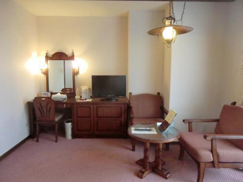 壁側にデスク、テレビ、そして、小さなテーブルと椅子が置かれている。パソコンを開くにはデスクが狭い気がする。<br />