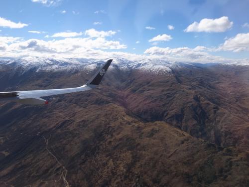 飛行機が滑走路に向けて出発したかと思ったら、途中で搭乗口まで戻り、<br />急病人を説き伏せて飛行機から降りてもらうハプニングあり。<br />1時間以上遅れての離陸となりました。<br /><br />フライトは揺れもなく、機内の安全ビデオで大いに楽しみました。<br />ニュージーランド航空の安全ビデオはぴか一です!<br />YouTubeでも視聴できますので、ぜひ見てください。おすすめです。<br /><br />さて、クイーンズタウン空港へもうすぐ着陸します。<br />峡谷に沿って高度を下げていきます。ちょっと怖い・・・