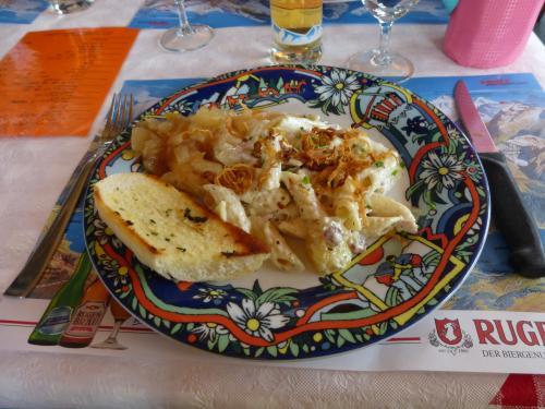 下山後、昼食になりました。<br /><br />山岳地方の名物料理「アルペンマカロニ」<br />このツアーの昼食で、一番おいしかった!<br />(添えられているのは、ガーリックパン)<br /><br />それと、お皿がかわいらしかったです。<br />(1枚、1枚、違う柄だった。私のは、きっとエーデルワイスの柄ですね)<br />ハイキングの後、アルプスの山を眺めながらの昼食。ということもあったのかもしれません。<br /><br />ここではデザートにプリンが出ました。<br />日本のプリンと全く同じ!おいしかったです。