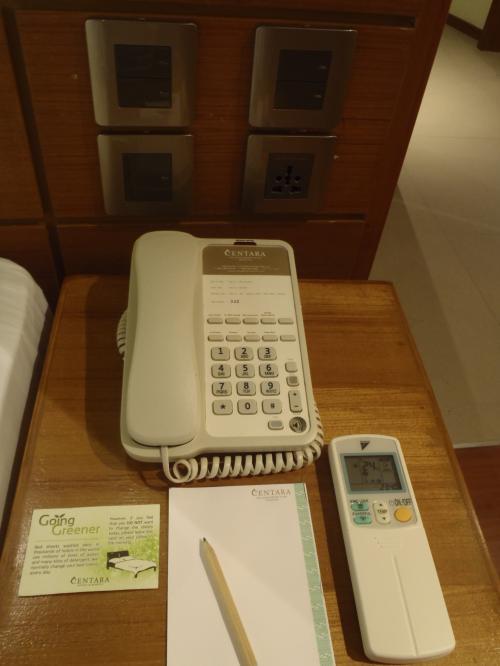 ベッドの横には電話、エアコンのリモコン、メモ帳があります。