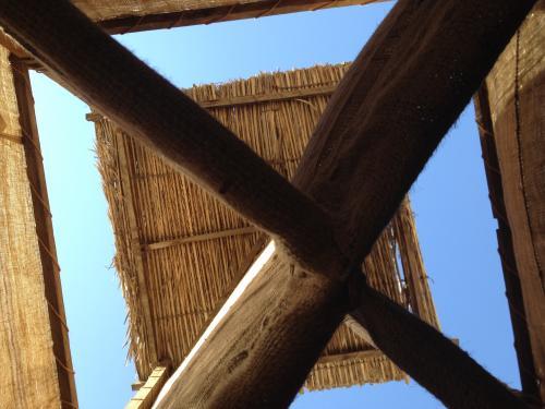 昔の家屋はナツメヤシの幹や葉っぱで作られている。<br />年に2日くらいしか雨が降らないそうで、水は井戸から調達。<br />これは家の天井に作られている風塔を下から覗いたところ。<br />真ん中に十字で仕切っている布があり、東西南北から風を取り込んで部屋に流れ込むように作られている。<br />頭いい〜!