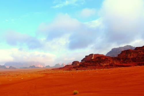 曇りがちだった空にも青空が見え始め、砂漠の赤い砂が輝き始める。<br />ベドウィンのお兄さんが運転するトラックは、風をきり砂漠を走り抜ける。<br /><br />私と母は、寒さ対策にダウン・ジャケットの上に更にゴアテックスの雨具を着用し、かなりモコモコ状態。更に手袋も。そのおかげで、全然寒くなかった。<br /><br />母と二人、トラックの荷台の上に立ち上がり、運転席の屋根の上から顔を覗かせ、カメラを構え、景色を眺める。<br />ベドウィンのお兄さんに、映画アラビアのロレンスに出てくる銃撃手みたいと笑われる。