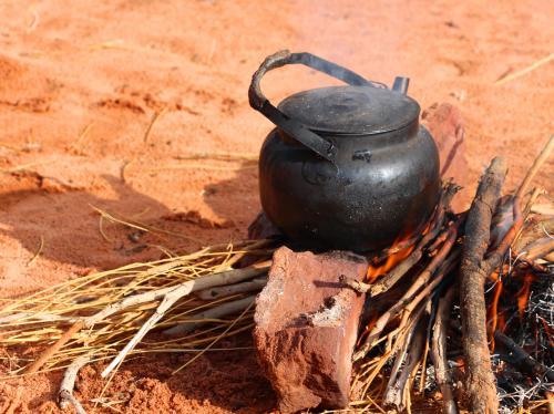 火がある程度大きくなったら、木の枝を集めてきて、更に石で五徳を作り、その上に鉄瓶を載せて、ティー・パーティの準備完了。<br /><br />赤い砂漠の中に、たき火の匂い、そしてベドウィン・ティの香りが仄かに漂う。<br />