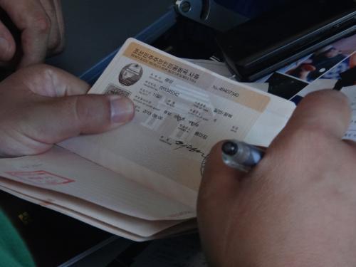 隣席の中国人が入国書類を記入するときビザを盗み見。凱旋門と国章が描かれたなかなかかっこいいビザじゃないですか!
