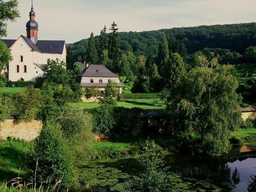 ;05.16(火)ラインガウ探訪<br /><br />≪Kloster Eberbachエーベルバッハ僧院≫<br /><br />1136年ベネディクト派から派生したシトー修道会がこの地に移住してきて、12世紀において最も影響力のある修道会に発展したと云う。<br />この僧院は現在ヘッセン州立のワイン醸造・販売機関になっているが、古い僧院の中は見るものも多い。切符売り場はワインの直売所でもある。<br />順に周ると、①Kreuzgang回廊は13世紀の創建、内庭をぐるりと囲んだ長方形のもの。右手の柳の木の下にBrunnenhaus泉の家があり、食事時に僧が手を洗った。今は泉だけが残る。<br />②信者用の食堂--12世紀。今はワイン文化を伝える大きな葡萄の搾り器が所狭しに置かれていて、壮観である。<br />③Klosterkirche僧院教会は12世紀に創建されたもので、三部に分かれた身廊と南側に1340年完成のゴシック様式の礼拝堂、西の壁際には古い、珍しい事に表情豊かな人物画が彫られた墓碑が立てかけられている。現在はコンサート会場にも利用されるそうだ。<br />二階に上がると、④Kapitelsaal集会場にはゴシック様式の星型天井、蔓草模様画が見られる。<br />⑤僧侶達の寝室。<br />⑥厨房と図書室は1995年以来、僧院博物館として、各種の宝物、文書が展示されている。