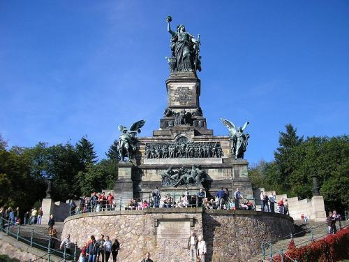 """像の下部には、""""ラインの守りDie Wacht am Rhein""""の歌が碑文になっていて、特に繰り返し歌われる文言が大きめに彫られていた。<br /><br />【Lieb Vaterland.Magst Ruhic Sein.Fest und Treu Die Wacht.Die Wacht Am Rhein.】と読める。【愛する祖国よ、平和であれ!ラインの守りは確かに、終始変らず!!】<br /><br />台座からの高さは凡そ10m弱でしょう。晴れた空の下、剣を持った女神がライン川を見下ろしています。左右に軍神が立ち、碑文の下にはラインの男女の神が船に乗っている姿が見られる。<br /><br />"""
