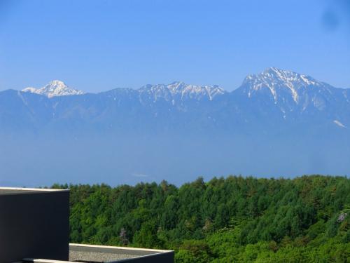 遠くに雪をかぶった甲斐駒ケ岳と北岳が見える。チェックイン後の至福のひと時をテラスで過ごす。