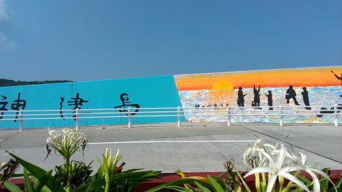 港近くの防波堤にも手書きの絵がありました。<br />手前に咲いているのは、島でよく見た花。「ハマユウ」というらしい。
