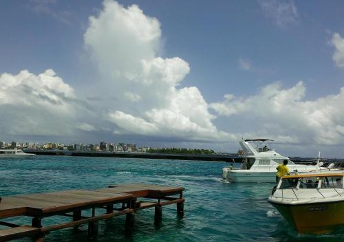 遠くに見えるビル群がモルジブ共和国の首都マレですね。<br />ほんと海抜ゼロ?。<br />島にビルがひしめいて建っています。