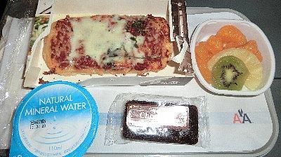 機内食:到着前の軽食(ピザ)<br /><br />友人とはマイルを使う航空会社が異なるために、現地集合・現地解散の旅となりました。帰りも別々にニューヨークへ行って合流し、また別々に帰国します。孫もいるおばあさん達ですよ、頼もしいでしょう?