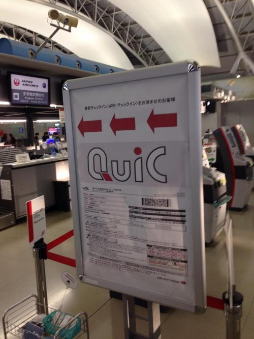 """JALのチェックインカウンター(F)前です。<br />事前にウェブチェックインを済ませてあったので、この看板""""QuiC""""のレーンから荷物(スーツケース)を預けます。"""
