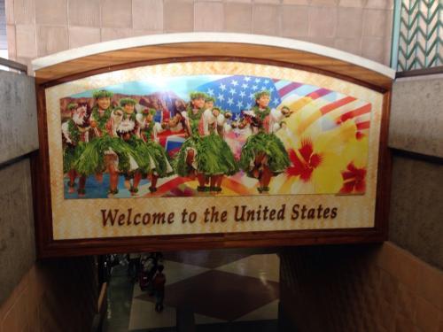 """空港ターミナル内に入ると、ハワイらしいフラガールたちが描かれた看板が""""Welcome to the United States""""とお出迎え。"""