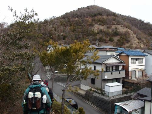脇に住宅が、びっしりと。<br /><br />結構急な登りが連続するので、暑くなって、衣類調節する方も。