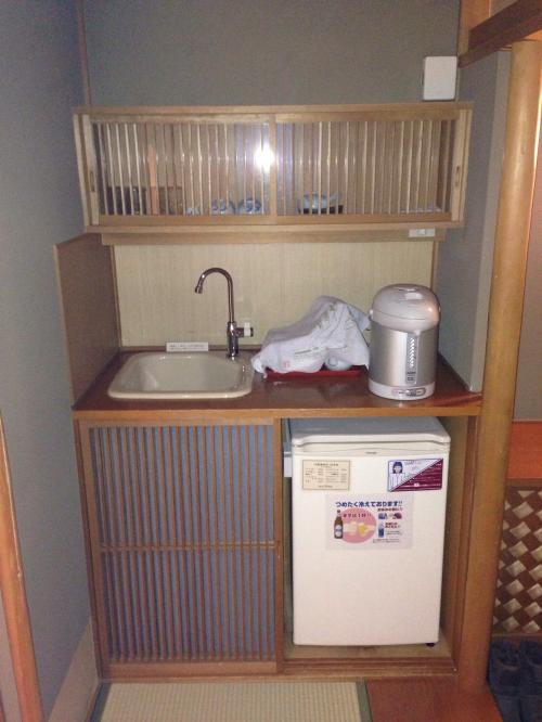部屋の入り口から靴を脱いで上がった場所(踏込?)には、冷蔵庫やポットなどが。