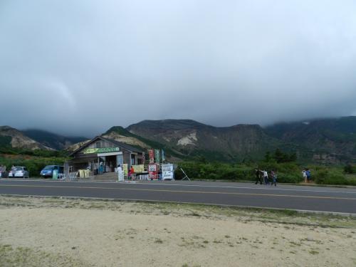 駐車場から道路を隔てたところに茶店があり、その向こうに蔵王山の風景が見えています。