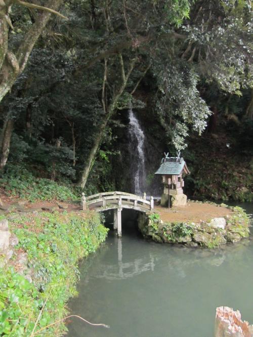 「心宇池」と後ろを流れる「亀の尾の滝」。<br />石橋の先には「天神社」があります。