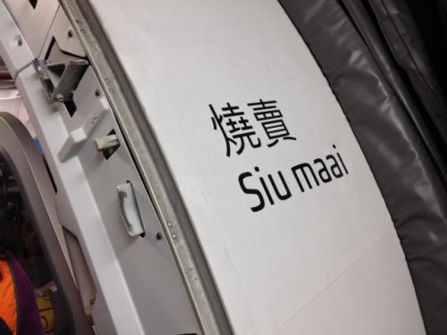 搭乗の時、扉の右側には「焼売」の文字が。「何だこりゃ?」と思って帰国後に調べてみたら、HKエクスプレスでは7機所有しているエアバス320の機体のうち、5機に「点心」に関わる名前をつけて運行しているらしい。これはそのうちの1機の「シュウマイ号」というわけ。 <br />