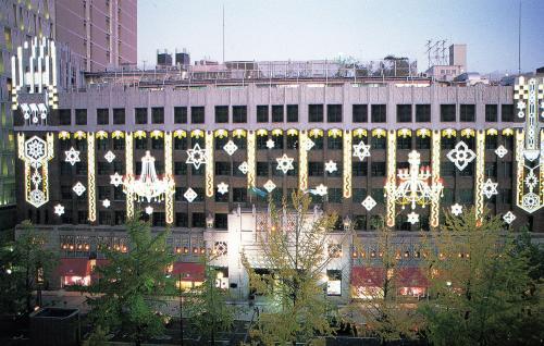 <大丸心斎橋店の建物全体の姿><br /><br />地下鉄心斎橋駅を降りると、そのまま地下道で大丸百貨店につながっていて、この日は雨が降っていたので、大いに助かった。<br /><br />この画像はクリスマス時のイルミネ−ションが施された御堂筋側から見た建物の外観である。白いイルミネーションが清楚な感じがして、美しい。
