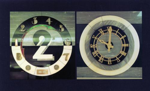 2階エレベターの前に取り付けられているもので、右側が時計で、左側はエレベェターの階数を示す指示板である。どちらもアール・デコ調のデザインである。 <br /><br />左側の階数を示す表示板に株が白い照明が付いているが、これは