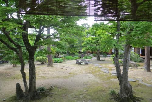 『大広間』の廊下からの眺めです。半ば巻き上げられた簾(すだれ)越しに眺めた庭の光景です正面左奥が池、更に左側が『御蔵』になります。