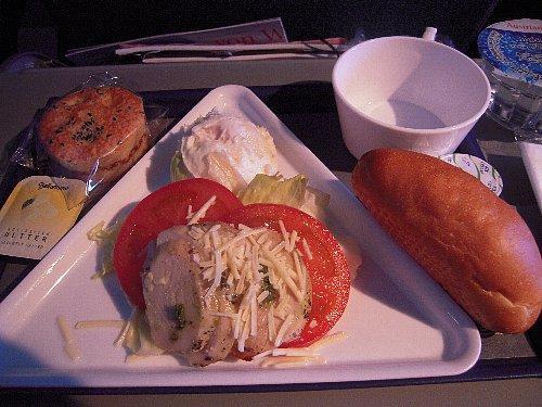 行きの機内食-2 朝食(サラダ、マフィン)<br /><br />機内食は美味しかったですよ。三角形のトレイが斬新でした。行きは夜食に、おにぎり・サンドイッチ1切れ・カップ麺のサービス(選択)がありました。