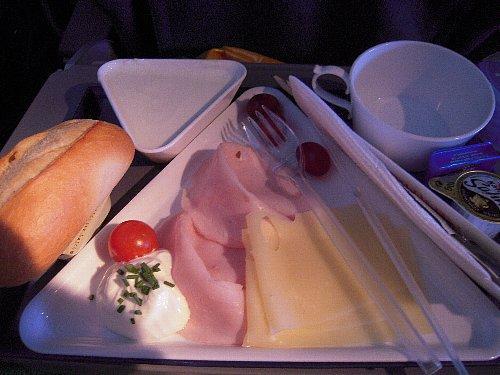 帰りの機内食-2 朝食(ハムとチーズ、ヨーグルト)<br /><br />12時間近いフライトタイムなので、乗務員は交替で休憩を取ります。パイロットは普段は二人ですが、休憩時の交代要員が必要なので3人乗務になります。3番目に休憩を取った人が着陸30分前に起きてきて、日本人FAさんが「グーテン・モルゲン」と挨拶をしていました。(笑)