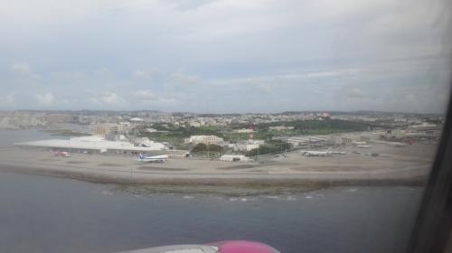 間もなく那覇空港に着陸。<br />この写真の左端にピーチの飛行機が止まってて、右側の旅客ターミナルとLCCターミナルの位置関係がよくわかりますね。<br />那覇のLCCターミナルは決して便利とはいえないけど、今どき使用料無料なのはステキ(^ ^)<br />でもバスはもうちょっと何とかしてほしいな…大きなスーツケース持ってる人も多いのに(バスに乗るのはチェックイン前or荷物受け取り後だから当然そうなる)、座席と段差が多い古い路線バスの車両だから、特に到着時はいつも大混乱…(> <)