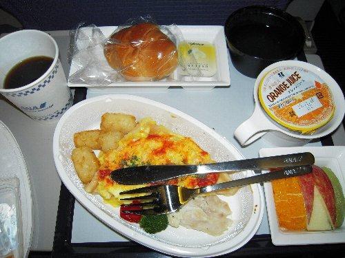 行きの機内食<br /><br />機内食は到着前の朝食になります。ワッフルの上にスクランブルエッグが乗っていました。<br />「お口に合いましたら嬉しゅうございます」 <br />さすが日本のCAさんは言葉使いが違うわね! でも料理は口に合わず、K子さんも「中途半端な味ね」とご不満でした。<br />珍しいことに金属製のナイフとフォークが出ましたよ。油断大敵、喉元過ぎれば暑さ忘れる?<br />何年か前までは、アメリカの同時多発テロの影響で機内では武器になる食器は撤去され、暫くはプラスチックでした。