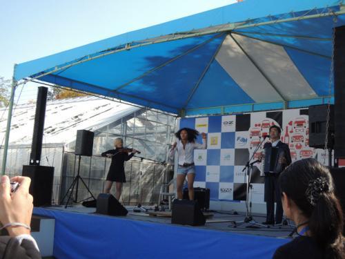 ステージには、前夜祭と同じメンバーの演奏が始まっていた。左から、Reina Kitadaさん(ヴァイオリン)、レオナさん(タップダンス)、田ノ岡三郎さん(アコーディオン)。