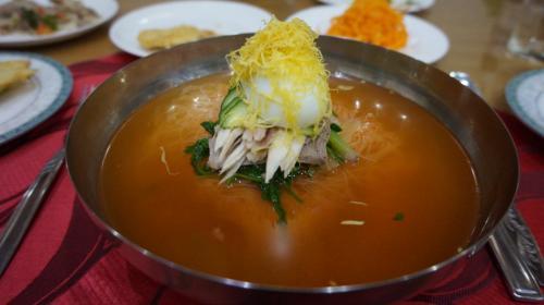 2日目 元山⇒咸興<br /><br />朝鮮・韓国には2大冷麺があるのをご存知ですか?<br />ひとつは平壌冷麺、もうひとつがなんと!咸興冷麺なんです!<br />すなわち、韓国で食べられてる冷麺も発祥はすべて朝鮮なんです!<br />味ははっきり言って美味いです。<br /><br />