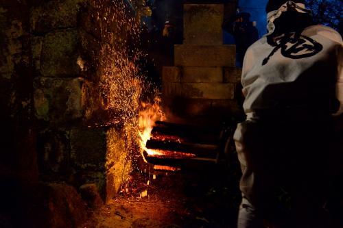松明を鳥居の石垣にぶつけ、火の粉を落とします。