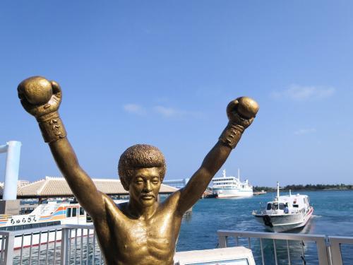 石垣島といえば島の英雄具志堅さん<br />離島フェリーターミナル<br /><br />-あんた誰さあ?-<br />「僕さあ、ボクサー」<br /><br />ここから各島々へ高速船やフェリーが出ている。八重山の中心だ。最近では台湾や中国からも大型クルーズ船がきている。今宵は久し振りにジンマミー揚げ出し豆腐が食える<br /><br />●美味しいには二種類あって、喉や舌が感じるものと身体自体が欲するものである。後者を感じるようになって、初めて食というものがわかってくる。<br />身体は今生きていくのに必要な食べ物・飲み物を美味しいと感じるように造られているのだ。舌・喉でいかに旨いものでも続けて食べればマズくなる。