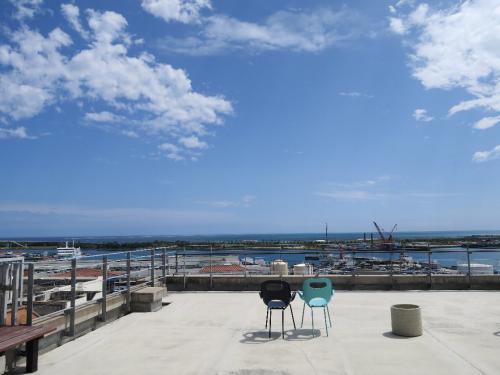 ホテル屋上から石垣港離島ターミナル<br /><br /> 今回の貴重な晴れ間、天気予報だとほとんど毎日が雨。 だけど傘を拡げたことはないのはどうして? 雨の日は出かけないのだ。