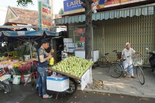 果物にスプレーする人、自転車を押しているオジサン、