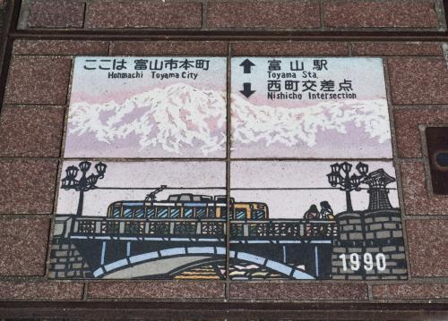 歩道に設置されたプレートには富山市内を走る電車が描かれている。