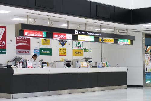 成田空港国際線ターミナル1F到着口を出て右にひたすら行くとレンタカーブースがあります。昨年の夏以降、すべてのレンタカーは空港ピックアップから周辺ピックアップに変更になりました。めんどくせぇ~