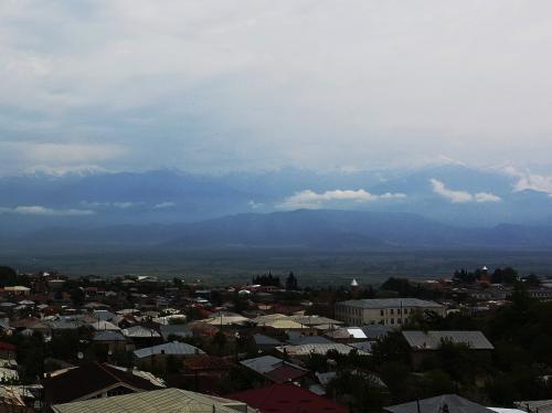 ディミトリさんちのテラスからみた風景。<br /><br />あいにくの曇り空ですが、遠くに雪を抱くコーカサス山脈がうっすらと見えています。