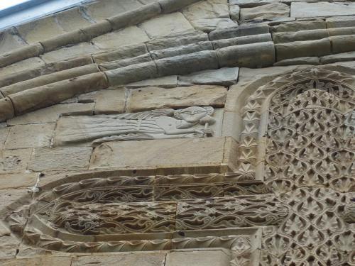 上の方、網目模様の十字架の上に、横向きの天使が飛んでいます。