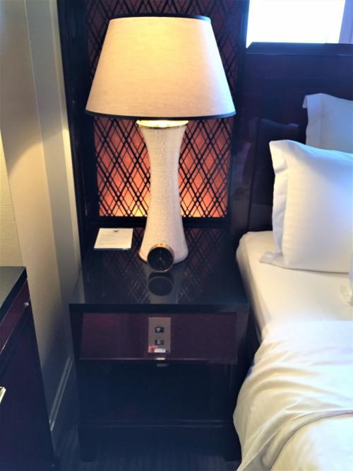 「クラブミレニアスイート」のベッド横(左側)に設けられたサイドテーブルの写真。<br /><br />ライトとメモ用紙、ミニ時計。下にティシュボックス。
