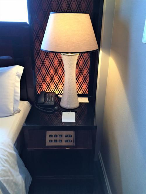 「クラブミレニアスイート」のベッド横(右側)に設けられたサイドテーブルの写真。<br /><br />ライトと電話機、メモ用紙。<br /><br />窓のシェードや部屋の照明を調整できるコントロールパネルが備えられています。