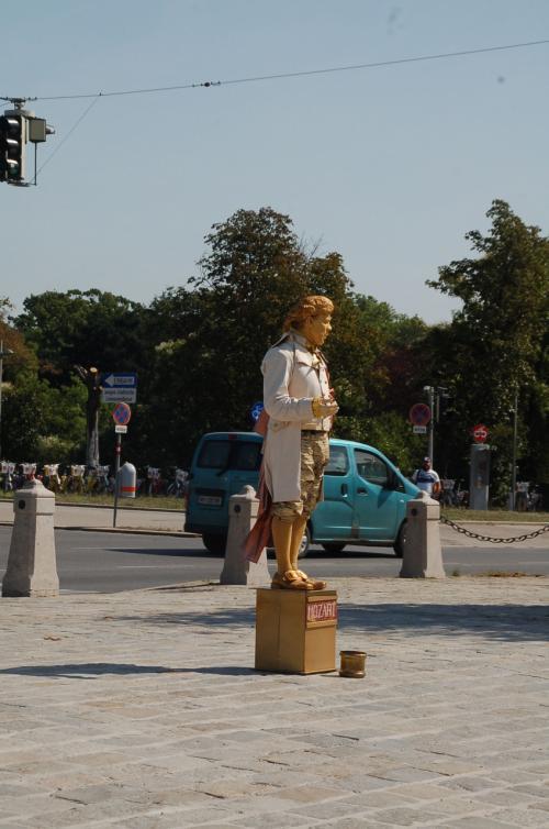 """ん? あれは? ヨーロッパで良く見掛ける大道芸人さんである。彼が立っている台には、""""Mozart""""と書かれている。どうやら、モーツァルトのふりをして立っているらしい。"""