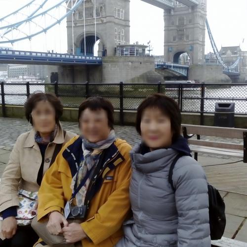 桟橋からタワーブリッジまでは500m以上歩かねばならないので、途中のベンチで休息がてら記念撮影。<br />橋脚の上に小さな小屋のようなものが見えますが、ここからロンドン・パスを使い、エレベーターで歩道橋部分に行きます。<br /><br />私たちの正面にはロンドン塔があります。<br />