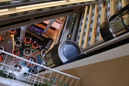 吹き抜けの内側に中層階までのカプセル型のエレベータ。上層階へは外側のエレベータで行く。