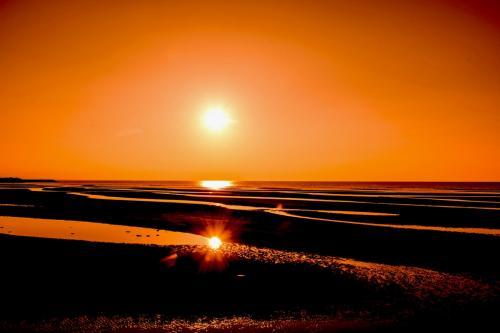 干潟から夕陽見物です。<br />夕日が、3か所に映ります。