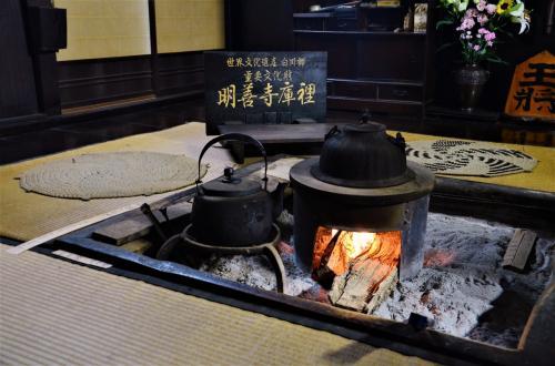 郷土館には囲炉裏があって火が焚かれています。<br />日本昔ばなしに必ず出てくる囲炉裏、心がホッと休まるようです。<br /><br />夏なのに薪を焚く、何かすっごい暑そうに聞こえますが、<br />実はこれ、茅葺きの屋根を維持するにはとっても大事なことなんです。<br />一つは防水・雨漏り対策。<br />煙に含まれる油分によって茅の表面がコーティングされるので、<br />茅葺きの内部に湿気が籠り腐敗するのを防止する効果があります。<br /><br />もう一つは防虫。<br />湿気がある茅葺きの中はヤスデやダンゴムシの格好のパラダイス。<br />湿気を除去するとともに囲炉裏や竈の煙で燻すことで、<br />虫が茅葺きの中に寄り付かない様に工夫しているのです (*゚∀゚)ノ<br /><br />理に適った先祖代々の素んばらしい知恵でございますが、<br />コストや手間、家中が燻蒸臭まみれになる等のデメリットも当然あり、<br />後継者不足の昨今、継続が難しくなっているのもまた事実です。