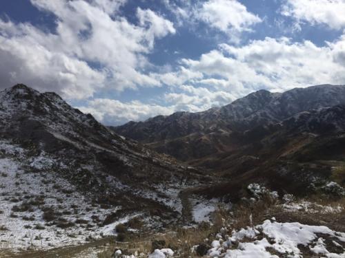 岩絵の後は、どんどん山岳地帯に入っていき、高度1,800mのビュー・ポイントで写真ストップ。<br />おー、いいね!<br />ゴツゴツした岩山に積雪。雄々しい風景だ。