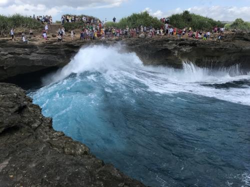 レンボンガン島では欠かせない絶景ポイント、デビルズティアーズです。<br />大勢の観光客が集まっています。<br />左側は波に侵食された洞窟のような形状の岩で、そこに大きな波が押し寄せます。<br />すると・・・