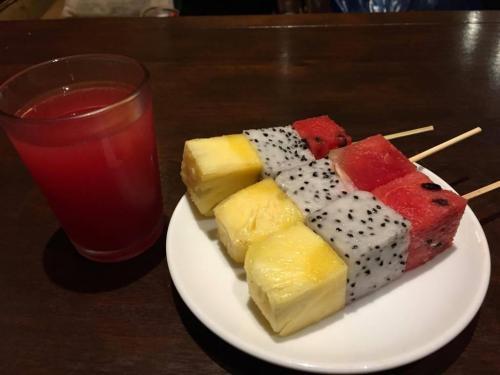 ホテルでのチェックイン時に頂いたウエルカムのフルーツとスイカジュース。真ん中にあるのは、定食メニューのデザートでおなじみのDGF(ドラゴンフルーツ)<br />