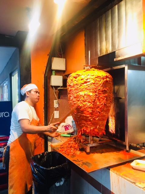 パストールというのは、豚肉をアチヨーテという香辛料とニンニク、そして、そのお店独自のスパイスを加えて漬け込んだのち、写真のような炭火で炙り焼きにする料理です。<br /><br />こいつを薄く仕上げたトルティージャに乗せて、シラントロ(パクチー)と玉ねぎ、パイナップルを載せて出来上がり。<br /><br />