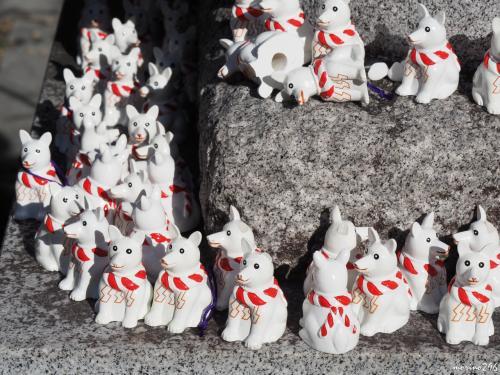 伊奴神社 犬石像の足元に並ぶ「いぬみくじ」の犬